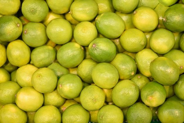 Frische grüne kalke der lebensmittelfrucht, hintergrund. frisches imes muster für verkauf im markt Premium Fotos