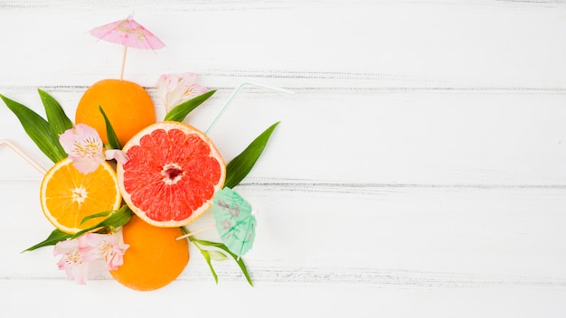 Frische grüne pflanzenblätter und zitrusfrüchte unter blumen Kostenlose Fotos