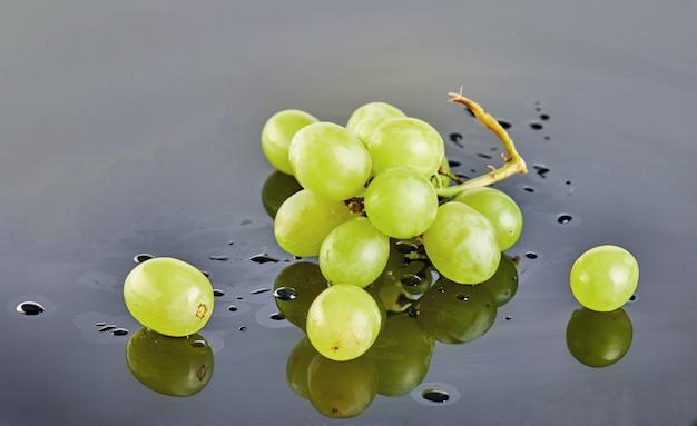 Frische grüne trauben mit wasser fällt auf einen grauen hintergrund Premium Fotos