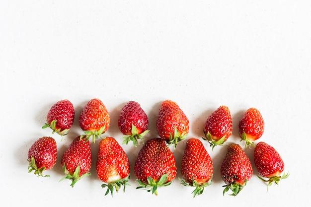 Frische hässliche reife erdbeeren liegen in zwei reihen unterschiedlicher größe Premium Fotos