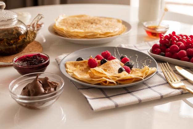 Frische hausgemachte appetitliche crepes mit beeren und honig auf teller, schalen mit kirschmarmelade und schokoladencreme, teekanne und reifen himbeeren Premium Fotos