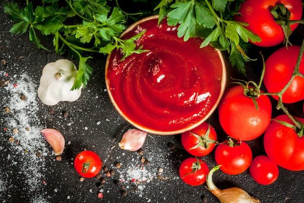 Frische hausgemachte bio-tomatensauce oder ketchup in einer kleinen schüssel mit den zutaten - petersilie zwiebeln knoblauch tomaten salz pfeffer auf einem schwarzen stein betontisch horizontal mit Premium Fotos