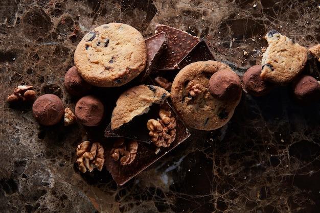 Frische hausgemachte schokoladenkekse mit pralinen in der dunklen marmoroberfläche. Premium Fotos