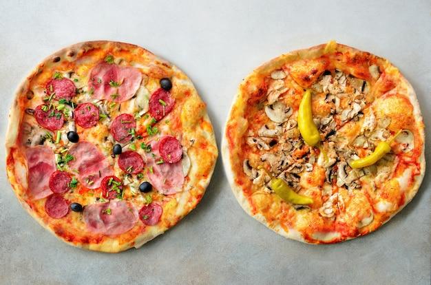 Frische italienische pizza mit pilzen, schinken, tomaten, käse, olive, pfeffer auf grauem konkretem hintergrund. Premium Fotos