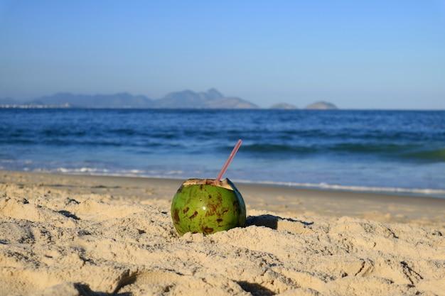 Frische junge kokosnuss auf dem sandigen strand copacabana in rio de janeiro, mit unscharfem atlantik im hintergrund Premium Fotos
