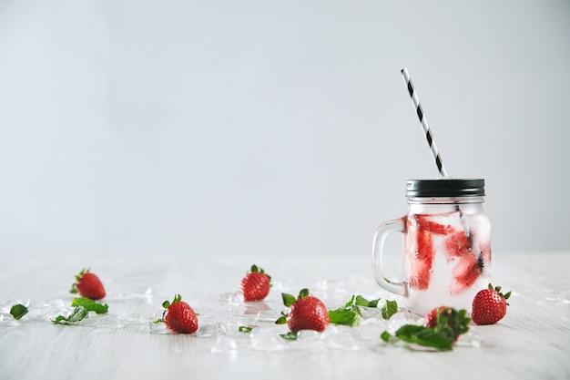 Frische kalte hausgemachte limonade aus erdbeere und mineralwasser im rustikalen glas mit streifenstroh lokalisiert auf weiß. Kostenlose Fotos