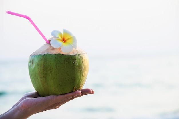 Frische kokosnuss in der hand mit dem plumeria verziert auf strand mit seewelle - tourist mit sonnenferienkonzept der frischen frucht und des meersands Kostenlose Fotos