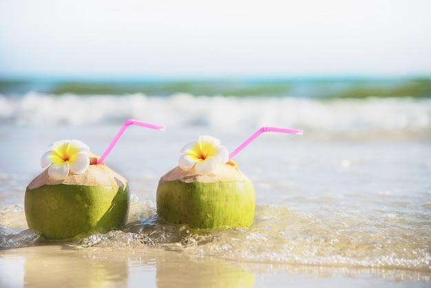 Frische kokosnuss mit der plumeriablume verziert auf sauberem sandstrand mit seewelle - frische frucht mit meersandsonnen-ferienkonzept Kostenlose Fotos