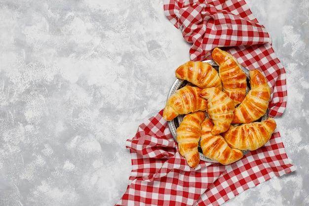 Frische leckere hausgemachte croissants auf grau-weiß. französisches gebäck Kostenlose Fotos