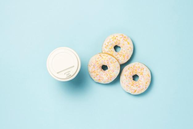 Frische leckere süße donuts und eine pappbecher kaffee oder tee auf blauem grund. fast-food-konzept, bäckerei, frühstück. minimalismus. flache lage, draufsicht. Premium Fotos