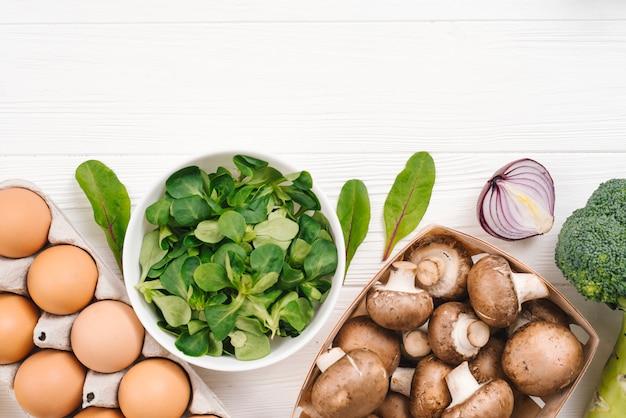 Frische maissalatblätter; eier; zwiebel; brokkoli und pilz auf weißem schreibtisch Kostenlose Fotos