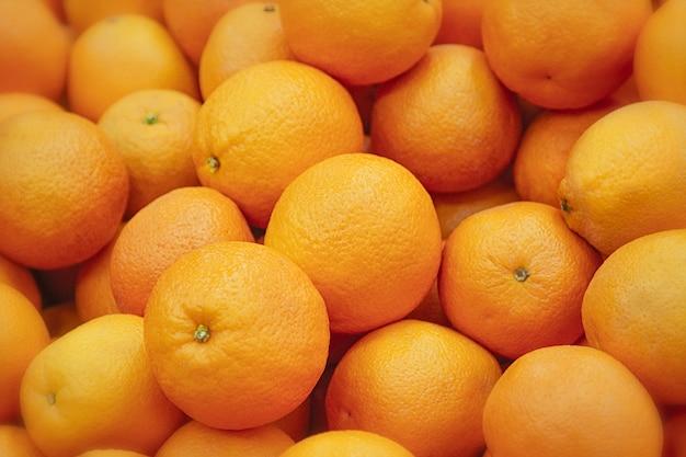 Frische mandarinen-textur. auf der theke liegende frische orangen - orangen- und mandarinenstruktur mit runden orangen und mandarinen Premium Fotos