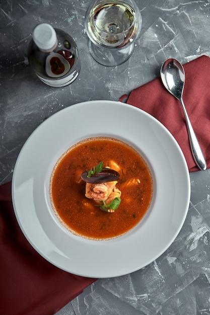 Frische meeresfrüchtesuppe in einer weißen platte auf dunklem hintergrund, draufsicht Premium Fotos
