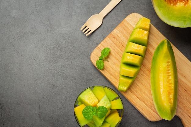 Frische melone, in stücke geschnitten, auf holzschneidebrett legen Kostenlose Fotos