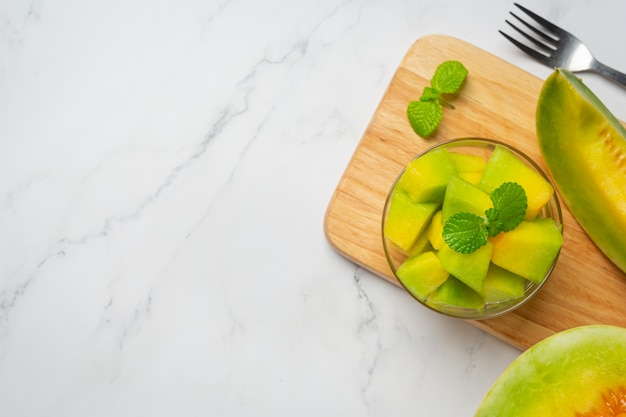 Frische melone, in stücke geschnitten, in eine glasschüssel geben Kostenlose Fotos