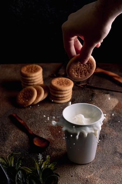 Frische milch mit selbst gemachten plätzchen auf einem holztisch, dunkler hintergrund. Premium Fotos