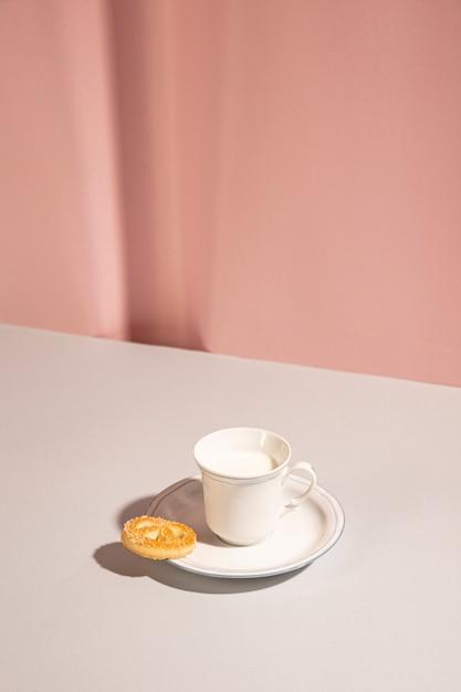 Frische milch mit süßem plätzchen auf tabelle gegen rosa hintergrund Kostenlose Fotos