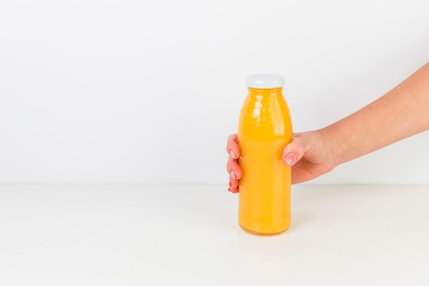 Frische orangensaftflasche mit weißem hintergrund Kostenlose Fotos