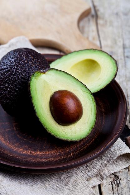 Frische organische avocado auf keramischer platten- und leinenserviette auf rustikalem holztisch Premium Fotos