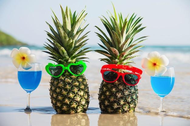 Frische paarananas mit sonnenbrillen und cocktailgläsern auf sauberem sand setzen mit seewelle - frische frucht und getränk mit meersandsonnen-ferienkonzept auf den strand Kostenlose Fotos