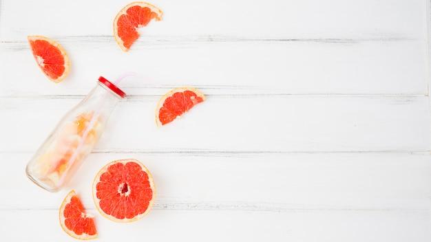 Frische pampelmusen und orangen in der nähe von flasche Kostenlose Fotos
