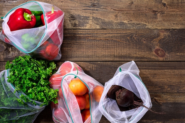Frische paprika, tomaten, rüben und gemüse in wiederverwendbaren umweltfreundlichen beuteln auf hölzernem braunem hintergrund mit kopienraum Premium Fotos
