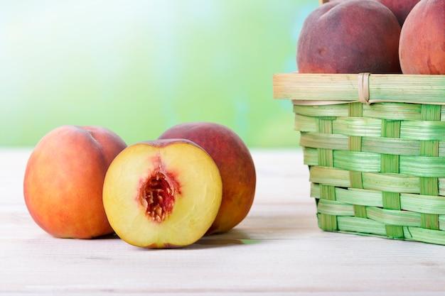 Frische pfirsiche auf einem holztisch nahe bei dem korb Premium Fotos