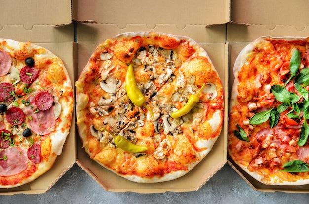Frische pizza im lieferungskasten auf grauem konkretem hintergrund. draufsicht, raum kopieren Premium Fotos
