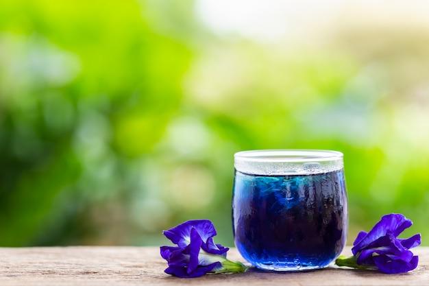 Frische purpurrote schmetterlingserbse oder blume und saft der blauen erbse im glas auf holztischhintergrund Premium Fotos