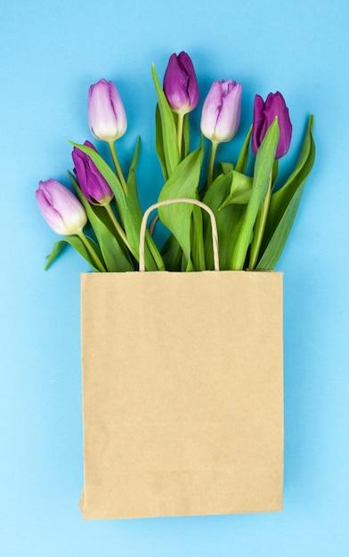 Frische purpurrote tulpe blüht im braunen papier über blauer oberfläche Kostenlose Fotos