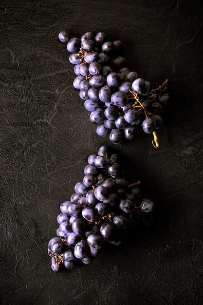 Frische reife bündel schwarze traubenbeeren auf küchentisch Premium Fotos