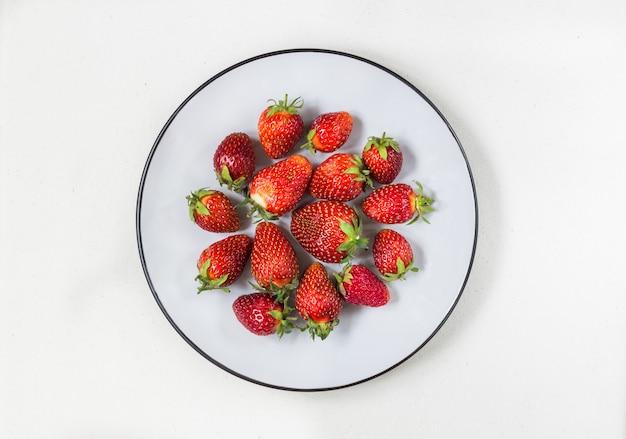 Frische reife erdbeeren in einem teller Premium Fotos