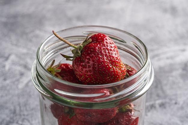 Frische reife erdbeerfrüchte im glas, sommervitaminbeeren auf grauem stein Premium Fotos
