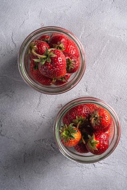 Frische reife erdbeerfrüchte in zwei gläsern, sommervitaminbeeren auf grauem stein Premium Fotos