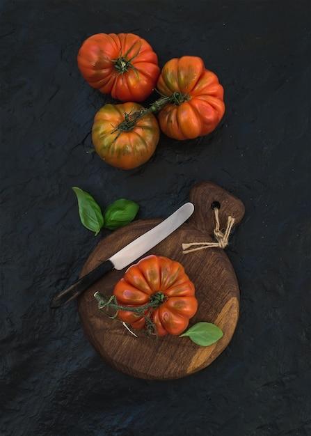 Frische reife hairloom tomaten und basilikumblätter auf rustikalem hölzernem brett Premium Fotos