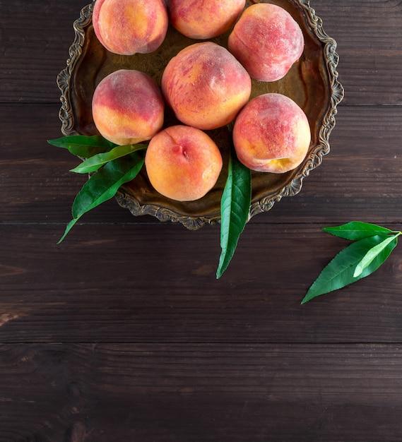 Frische reife pfirsiche in einer runden eisenplatte Premium Fotos