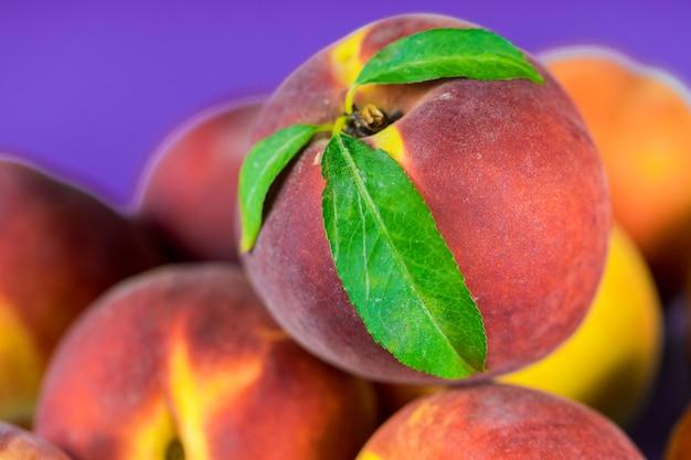 Frische, reife pfirsiche mit blättern schließen oben Premium Fotos