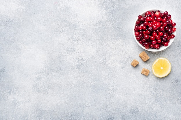 Frische rohe beerenmoosbeeren und -zitrone in einer platte auf einem grauen hintergrund mit kopienraum. Premium Fotos
