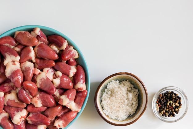 Frische rohe hühnerherzen und -gewürze auf weißer tabelle Premium Fotos