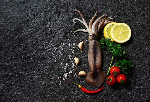 Frische rohe kalmarmeeresfrüchtekräuter und -gewürze mit zitronentomatenknoblauch Premium Fotos