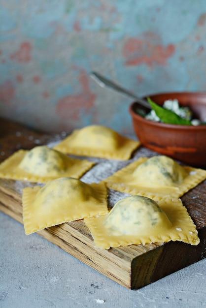 Frische rohe ravioli mit ricotta und spinat auf einem blauen hintergrund. Premium Fotos