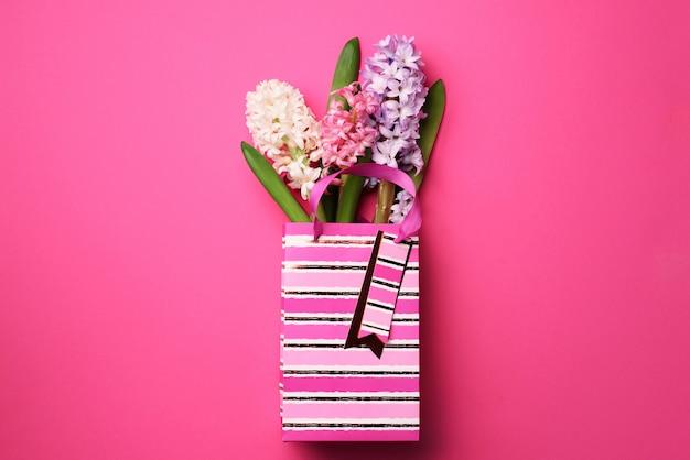 Frische rosa, weiße, violette hyazinthenblumen in der einkaufstasche auf schlagkräftigem pastellhintergrund. Premium Fotos