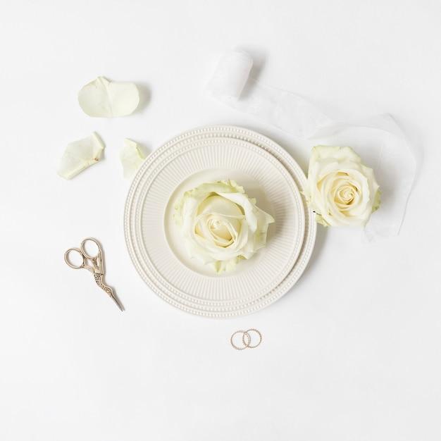 Frische rose auf teller mit band; schere und eheringe auf weißem hintergrund Kostenlose Fotos