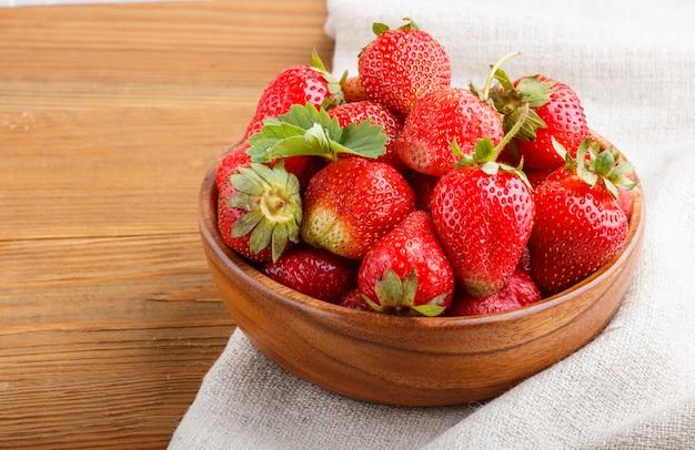 Frische rote erdbeere in der hölzernen schüssel Premium Fotos