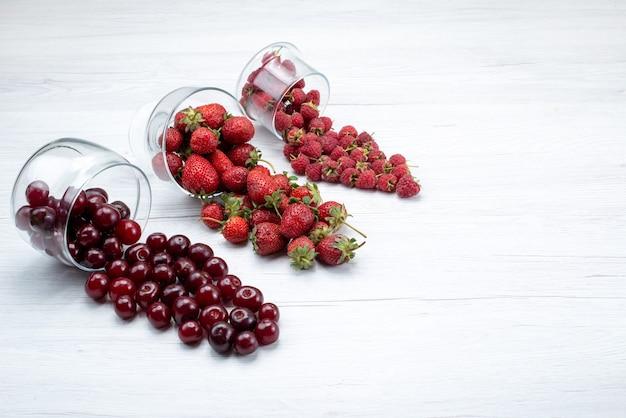 Frische rote erdbeeren mit sauren frischen kirschen und himbeeren auf licht Kostenlose Fotos