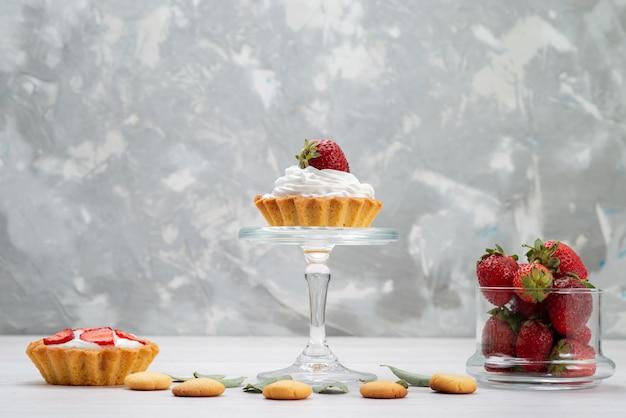 Frische rote erdbeeren weich und köstliche beeren mit kuchen und keksen auf hellem schreibtisch Kostenlose Fotos