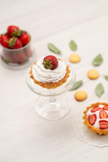 Frische rote erdbeeren weich und köstliche beeren mit kuchen und keksen auf licht Kostenlose Fotos
