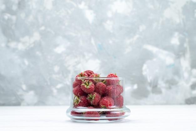 Frische rote himbeeren in transparenter schüssel auf weiß Kostenlose Fotos