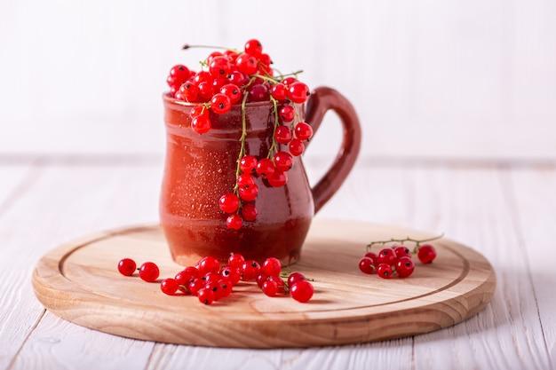 Frische rote johannisbeere in einer keramischen schale auf einem weißen hölzernen hintergrund Premium Fotos
