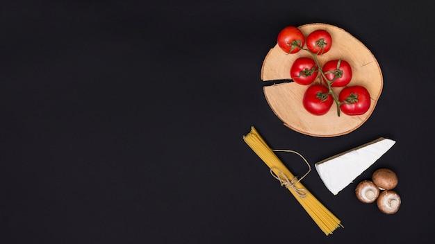 Frische rote tomaten; käse; pilz und bund spaghetti nudeln auf küchenarbeitsplatte Kostenlose Fotos